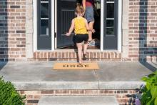 child walking in to home with parent through front door in summer