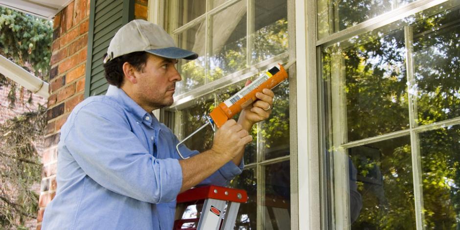 Home performance technician on a ladder air sealing window exteriors